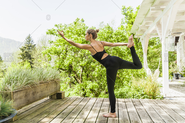Woman practicing yoga on wooden terrace