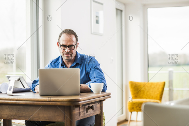 Businessman at home with laptop at wooden table