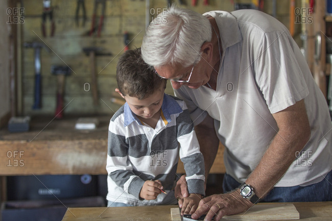 Grandfather and grandson working with wood in a garage