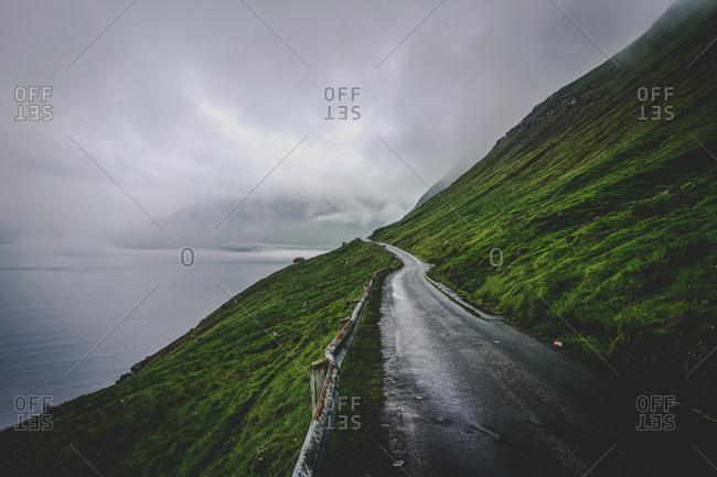Faroe Islands - July 27, 2016: Road leading to the beautiful mountainous landscape of the Faroe Islands
