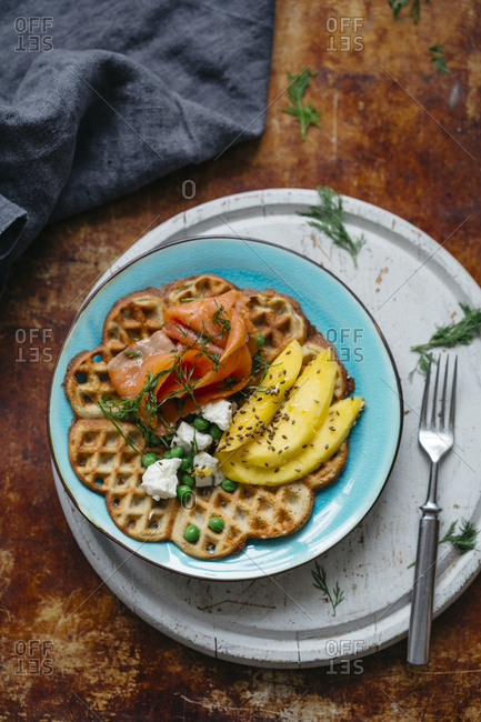 Salty delicious waffles on a plate with salmon, mango, dill and cream cheese, with natural light
