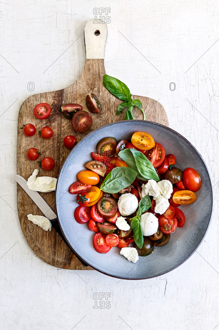 Tomatoes on chopping board with mozzarella