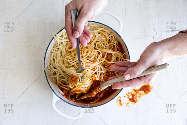 Spaghetti with meat sauce and hands dishing