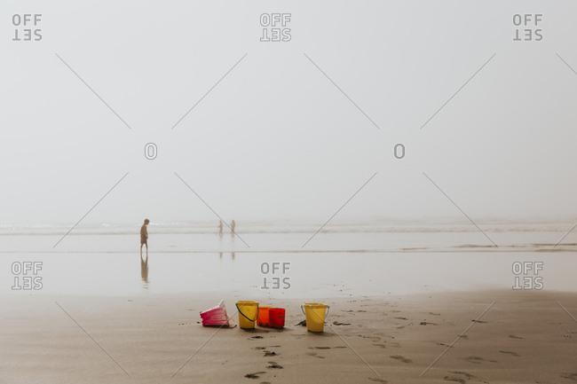 Sand buckets backlit on a sunny beach day
