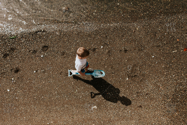 Overhead view of a young boy carrying a toy shovel on the beach