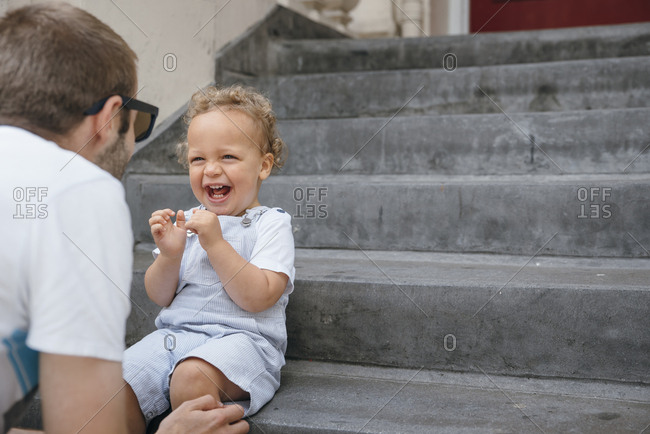 Young kid sitting on steps bursting with laughter