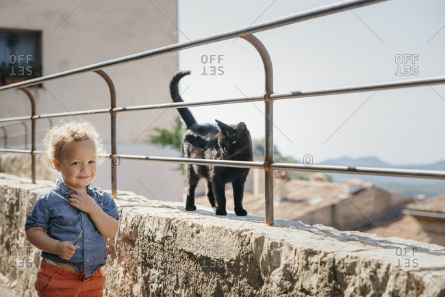 Black stray cat on street looking at young boy