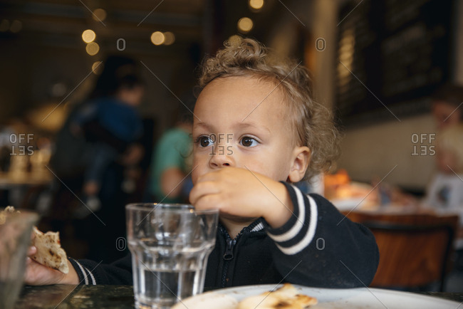 Pensive young boy drinking a glass of water with a straw