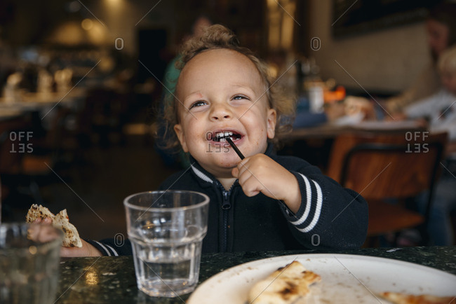 Young boy playing with a straw in restaurant