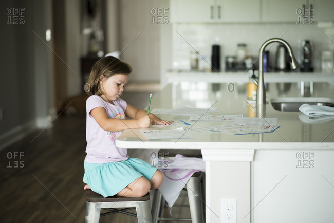 Little girl sitting at kitchen counter doing homework