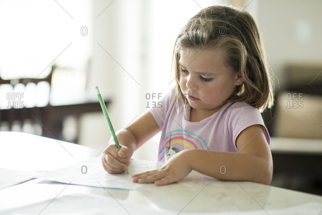 Young girl sitting at kitchen counter doing homework