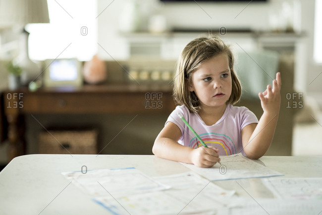 Young girl sitting at kitchen counter doing math homework