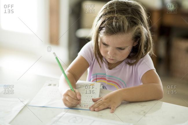 Girl sitting at kitchen counter doing homework