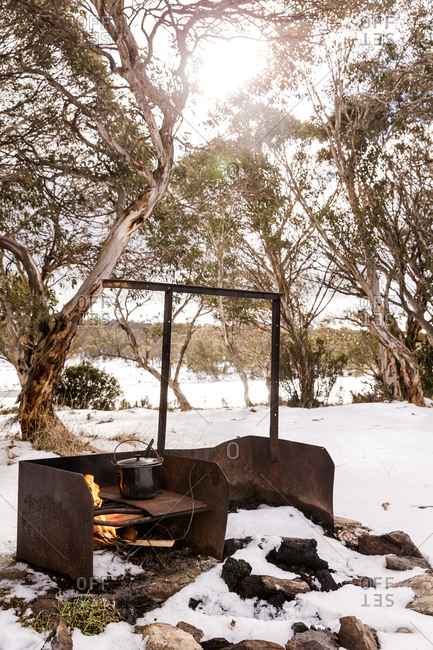 Outdoor winter scene with food on campfire