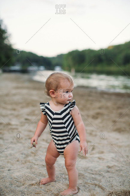 Toddler girl on river bank