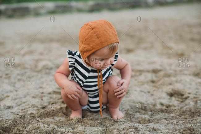 Toddler girl kneeling in sand