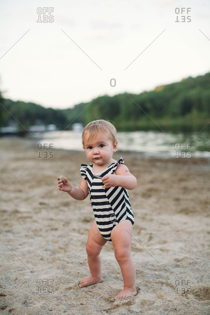 A toddler girl on river bank