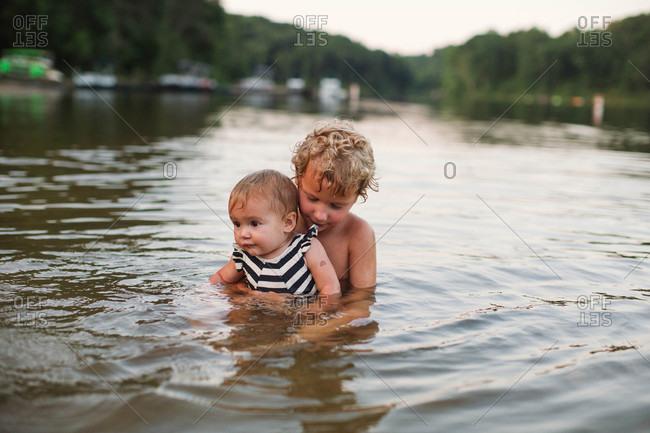 Boy holding toddler girl in river
