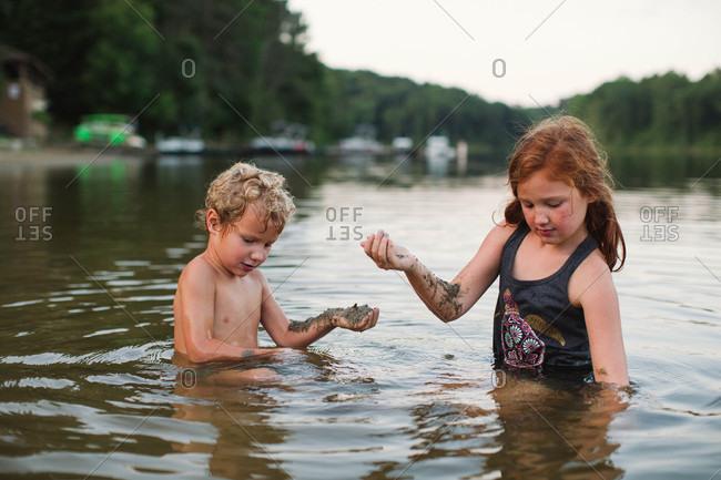 Kids picking up river mud