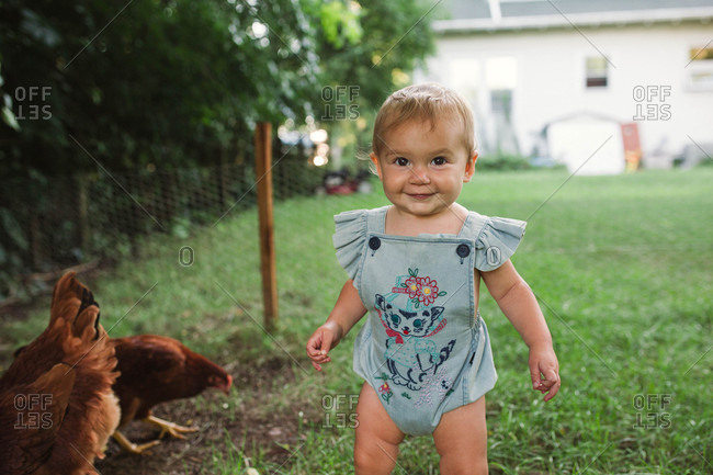Happy baby girl walking in grass with chicken
