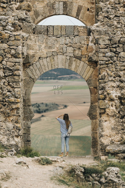 Woman looking out at view through arch at Gormaz Castle in Spain