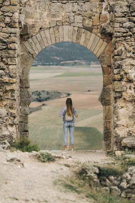 Rear view of woman looking out at view through arch at Gormaz Castle in Spain