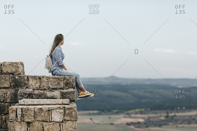Woman sitting on stone wall looking at view from Gormaz Castle in Spain