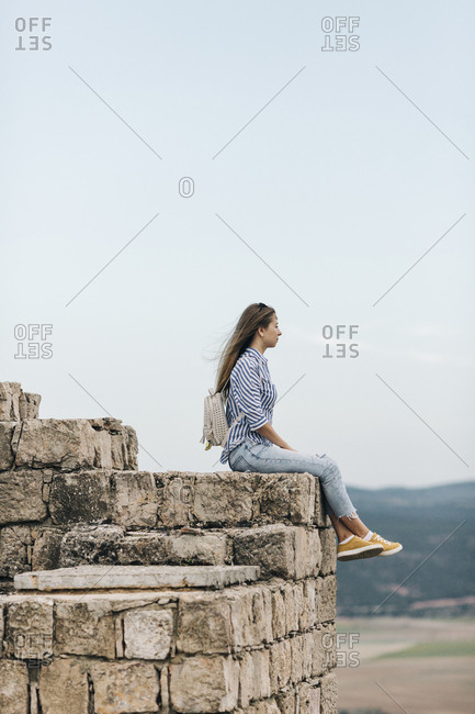 Young woman sitting on stone wall looking at view from Gormaz Castle in Spain