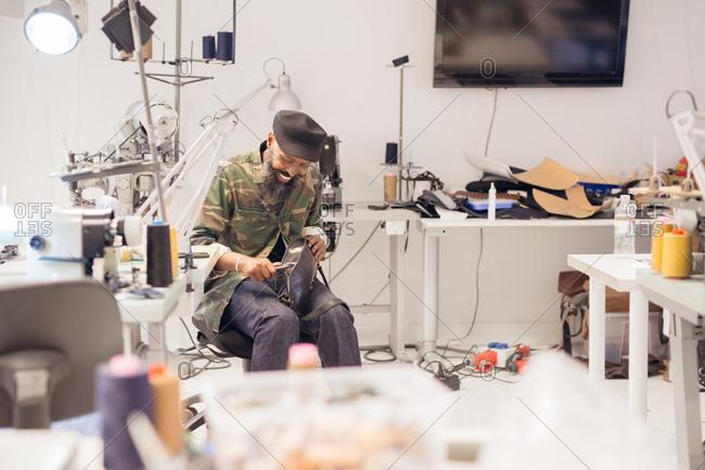 Man in studio making leather goods