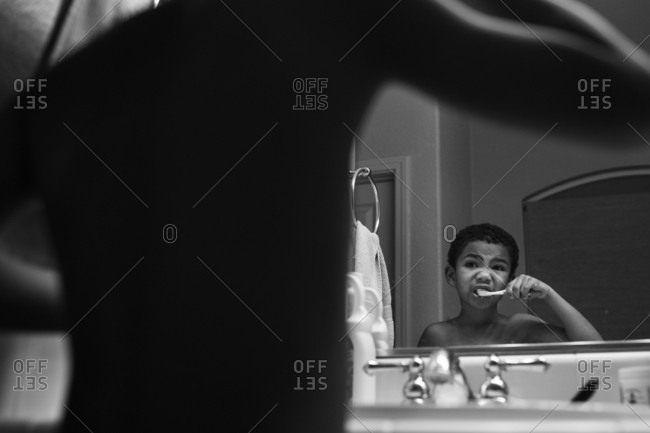 A boy brushes his teeth