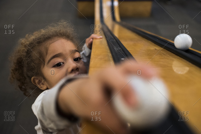 A girl plays with golf balls indoors