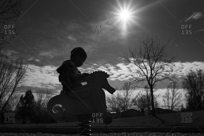 A silhouetted boy rides a toy seahorse