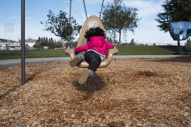A girl climbs on a playground swing