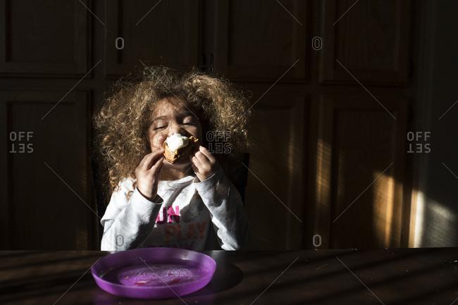 A toddler eats breakfast waffles