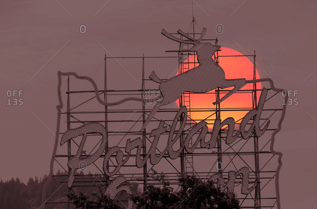 Sun behind sign for Portland, Oregon