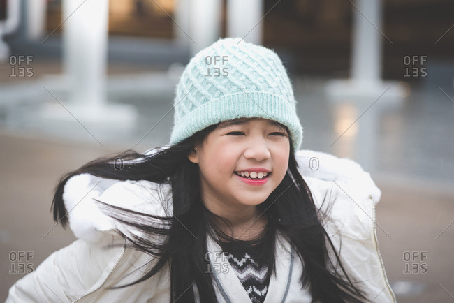 Close up of Asian girl enjoying a snowy day in the street