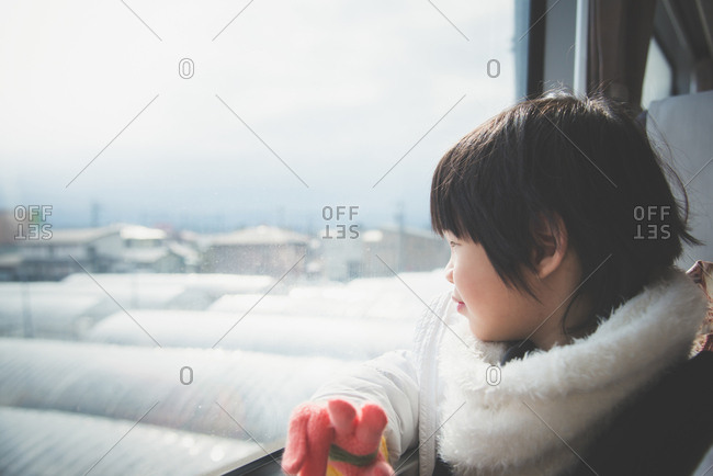 Happy Asian child looking out a train window