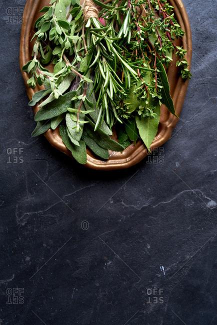 Food background variety of fresh green herbs on dark slate, healthy fresh ingredients
