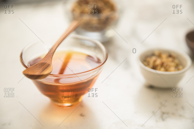 A bowl of honey with a wooden spoon