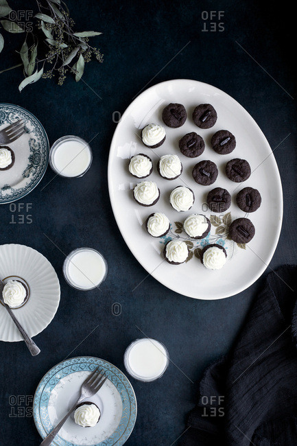 Brownie Bites with Orange Blossom Mascarpone Frosting served with milk.  Photographed on a dark blue background