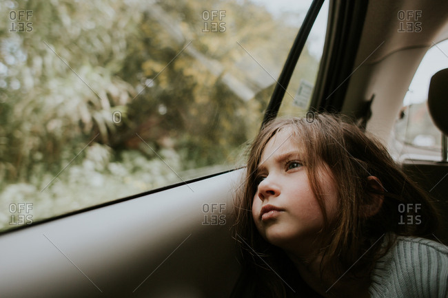 Little girl looking out window from backseat of car