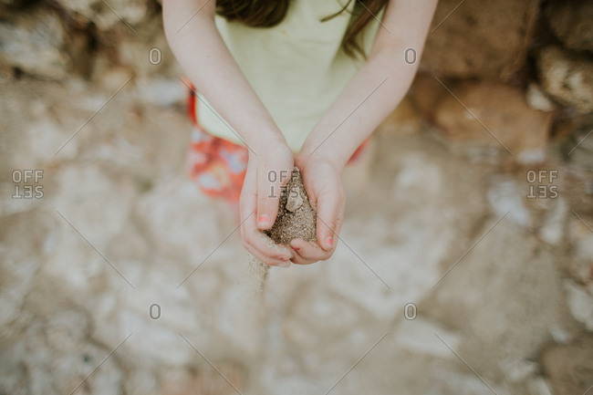 Overhead view of girl holding sand in her hands