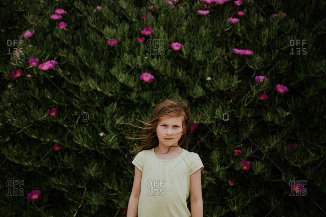 Young girl standing in front of bush with pink flowers
