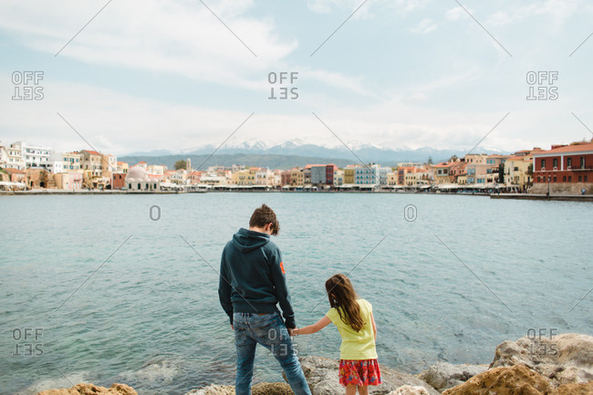 Brother holding little sister's hand while overlooking harbor in Chania, Crete, Greece