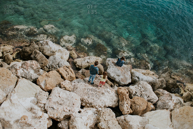 Siblings on rocky shore overlooking harbor in Chania, Crete, Greece