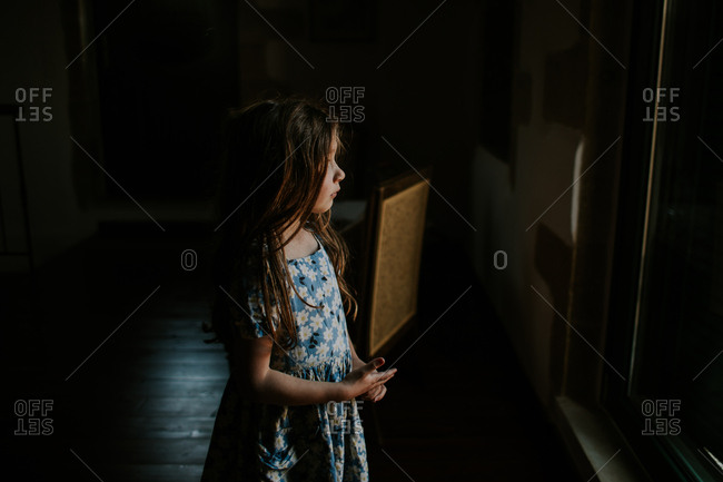 Young girl in floral dress looking out window