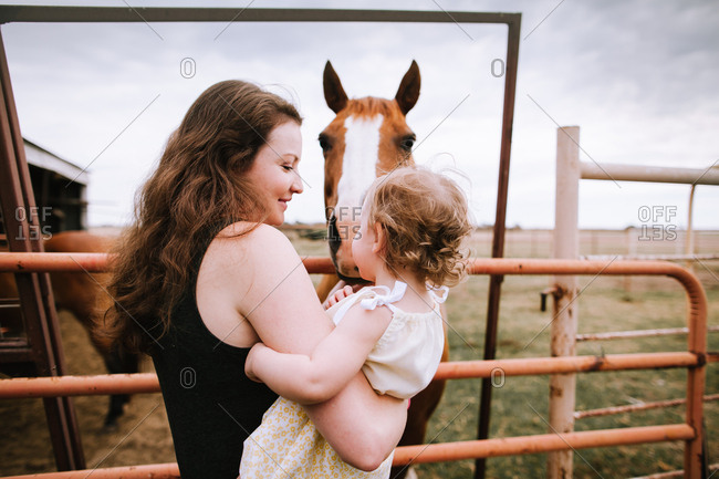 Woman and small child petting a horse