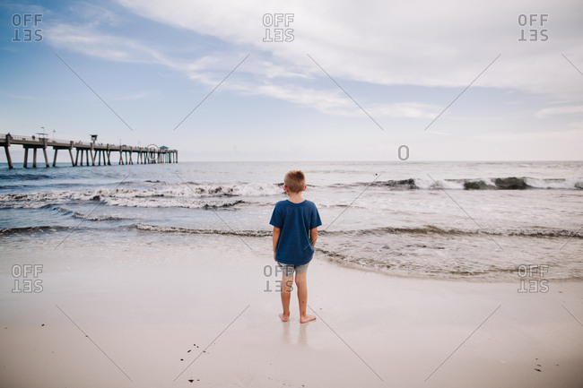 A boy standing on the beach