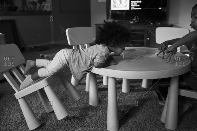 A toddler flips her chair in the living room
