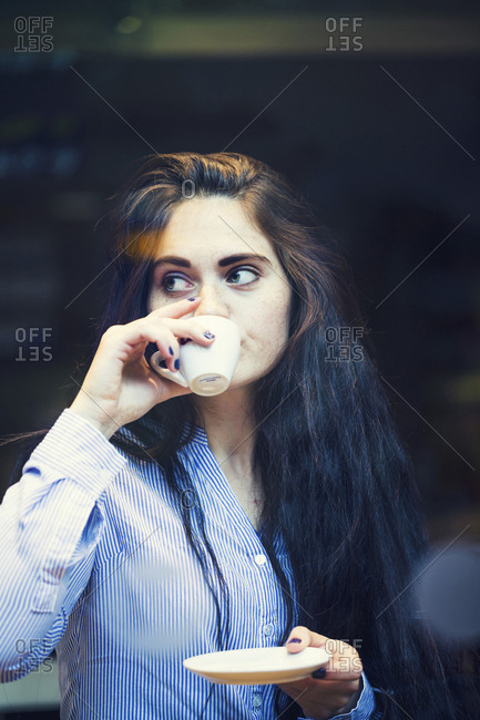 Curious Caucasian woman sipping coffee outdoors